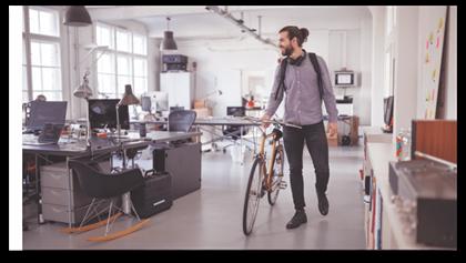 Empleado saliendo de la oficina con una bicicleta