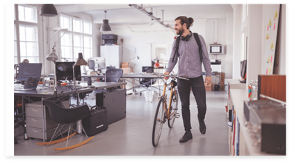 En medarbeider forlater kontoret på en sykkel