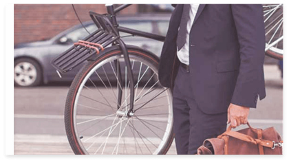 A guy with a suit a suitcase and a bike on his shoulder