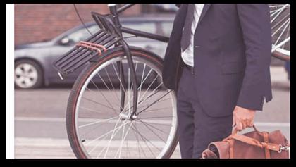 En mann i dress med koffert og med sykkel på skulderen