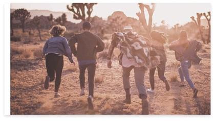 Een groep met vijf mensen rennend in de natuur