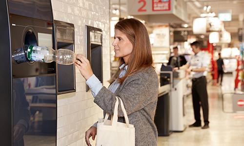Vrouw bij automaat voor geautomatiseerde inzameling van TOMRA