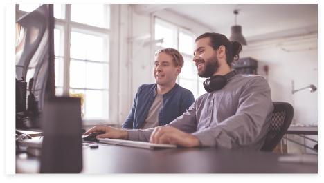 Zwei Mitarbeiter, die gemeinsam an einem Schreibtisch arbeiten