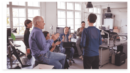 A group of employees listening and clapping to another colleague