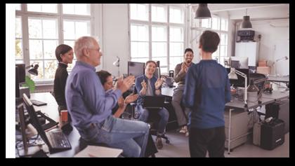 En grupp medarbetare som lyssnar på och applåderar en kollega