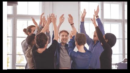 Een groep collega's op kantoor viert iets met de handen in de lucht