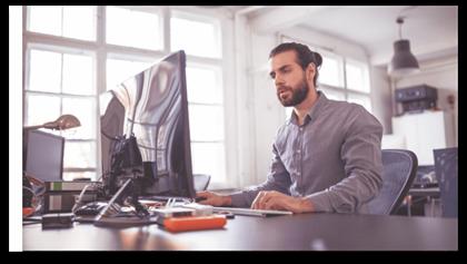 En medarbejder, der arbejder ved sin computer